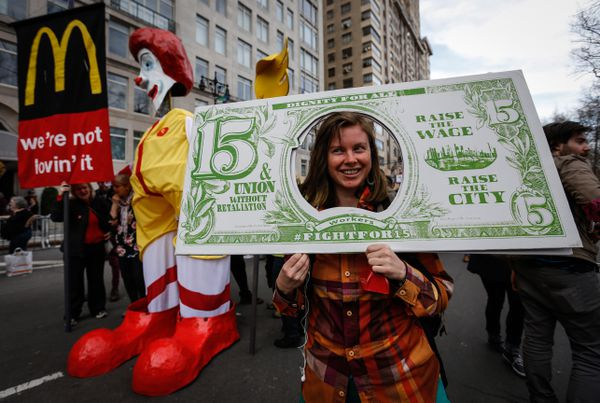 A woman holding a poster of a $15 bill during a Fight for 15 protest.