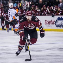 Bunting skates the offensive zone, eyeing the puck along the boards