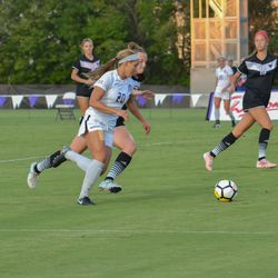 MANHATTAN, KANSAS - Kansas State forward Katie Cramer (20) dribbles as midfielders Brookelynn Entz (8) and Christina Wagner (19) look on during K-State's 2-0 victory over Omaha on August 30, 2017.