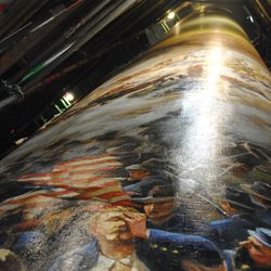 The painting is rolled on a spool to prepare for transport.