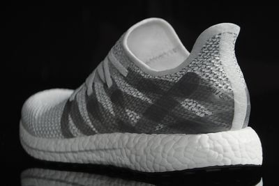 A white and grey Adidas sneaker on a black background, seen from behind. It looks almost like it's molded from a single piece of white rubber. It's a slip-on style with cross-hatched grey stripes over a smaller grey and white pattern similar to houndstoot