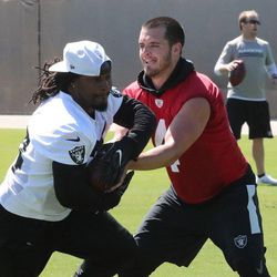 Marshawn Lynch takes a handoff from Derek Carr in Raiders offseason workouts