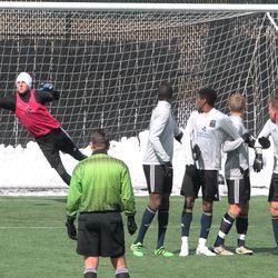 Jon Gallagher's free kick evades the grasp of Jake McGuire