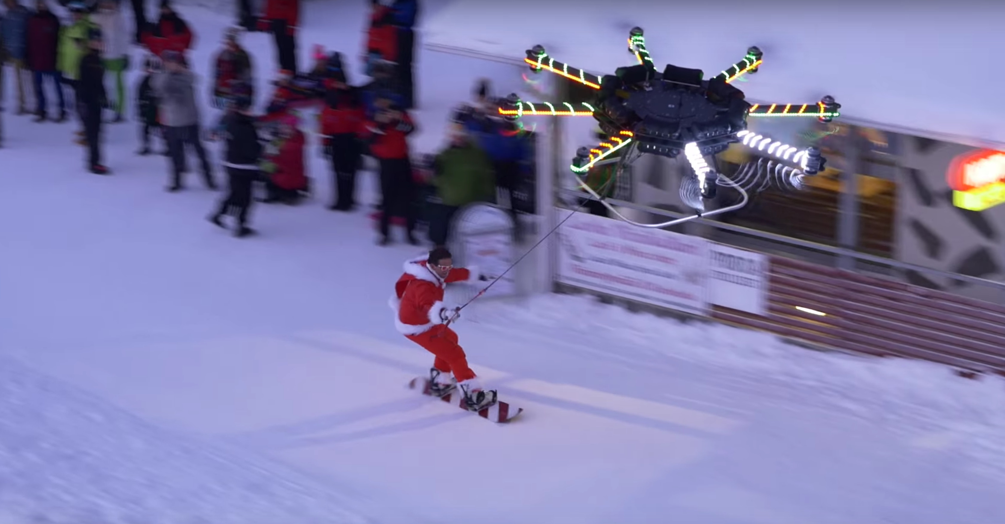 watch a human carrying drone lift a snowboarder off a mountain
