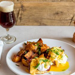 Braised bacon Benedict (biscuits, maple-glazed pork belly, smoked paprika hollandaise, poached eggs, breakfast potatoes).