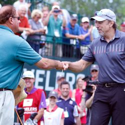 Actor Kevin Nealon (R) fist bumps Chris Berman after his tee shot at the 2017 Travelers Championship Pro-Am.<br>