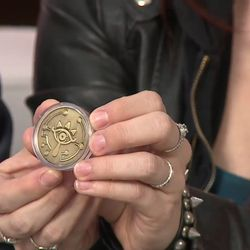 A close-up of the Sheikah Eye coin, which has the game's logo on the other side.