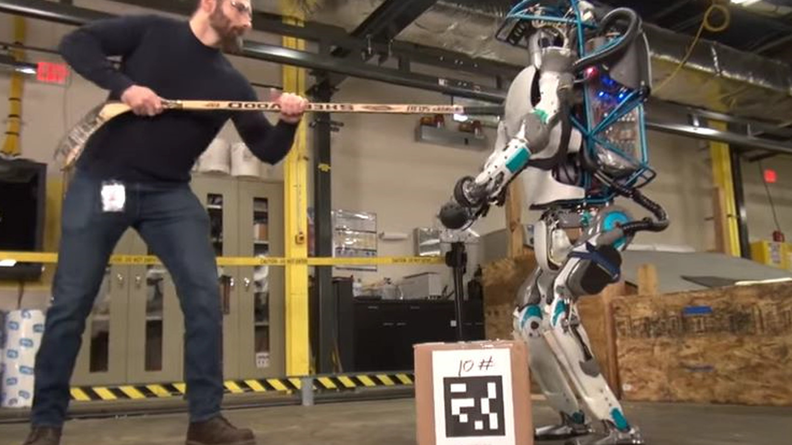 mean human uses hockey stick to bully hard working robot. Black Bedroom Furniture Sets. Home Design Ideas