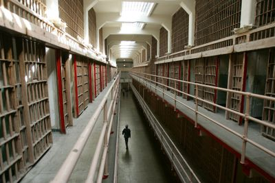 A National Park Service ranger walks down the main cell block of Alcatraz Island.