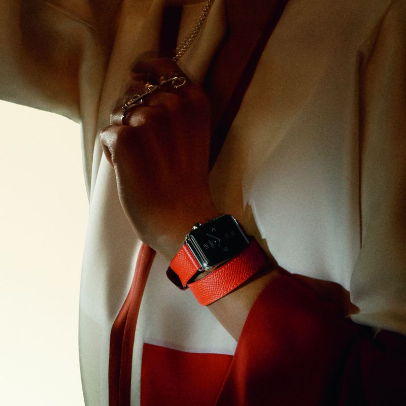 A female model dressed very retro-seventies wears an Apple Watch with an orange Hermès band.