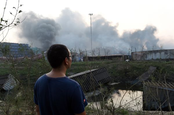 A man in Tianjin near the explosion looks at the site afterwards