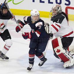 Team Canada goaltender Shannon Szabados touches Team USA forward Hannah Brandt.