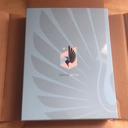 """AT LONG LAST. The outside of the packaging, featuring the team's beautiful logo, a glossy wing, and the slogan, """"Forever United."""""""