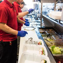 Taco Ssam crew members arranging ingredients in to-go boxes. <br>