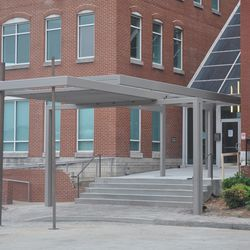 A new glass and steel canopy being installed at the building entrance.