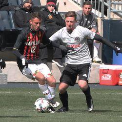 Jake Rozhansky on the ball with Aaron Jones defending