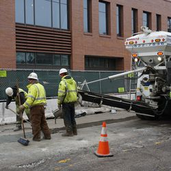 Concrete being poured on Clark Street, in front of the plaza building