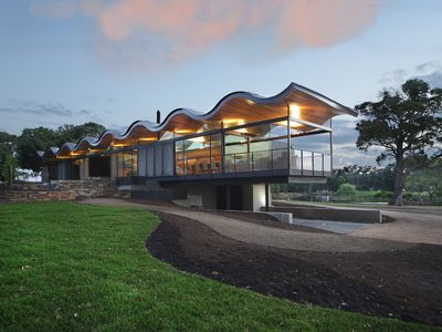 Modern glass house sports floating wavy roof