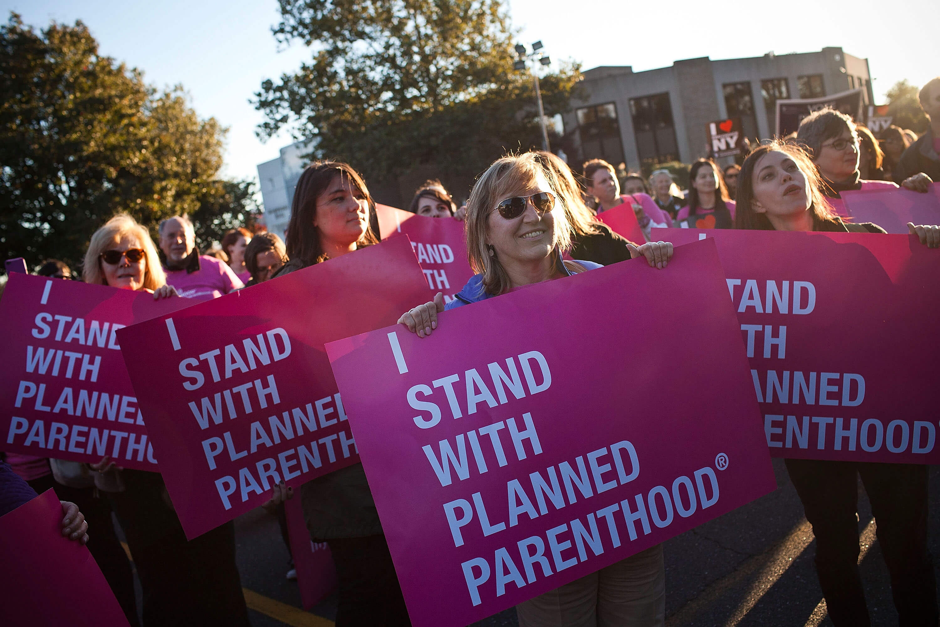 """A group of women holding """"I STAND WITH PLANNED PARENTHOOD"""" signs."""