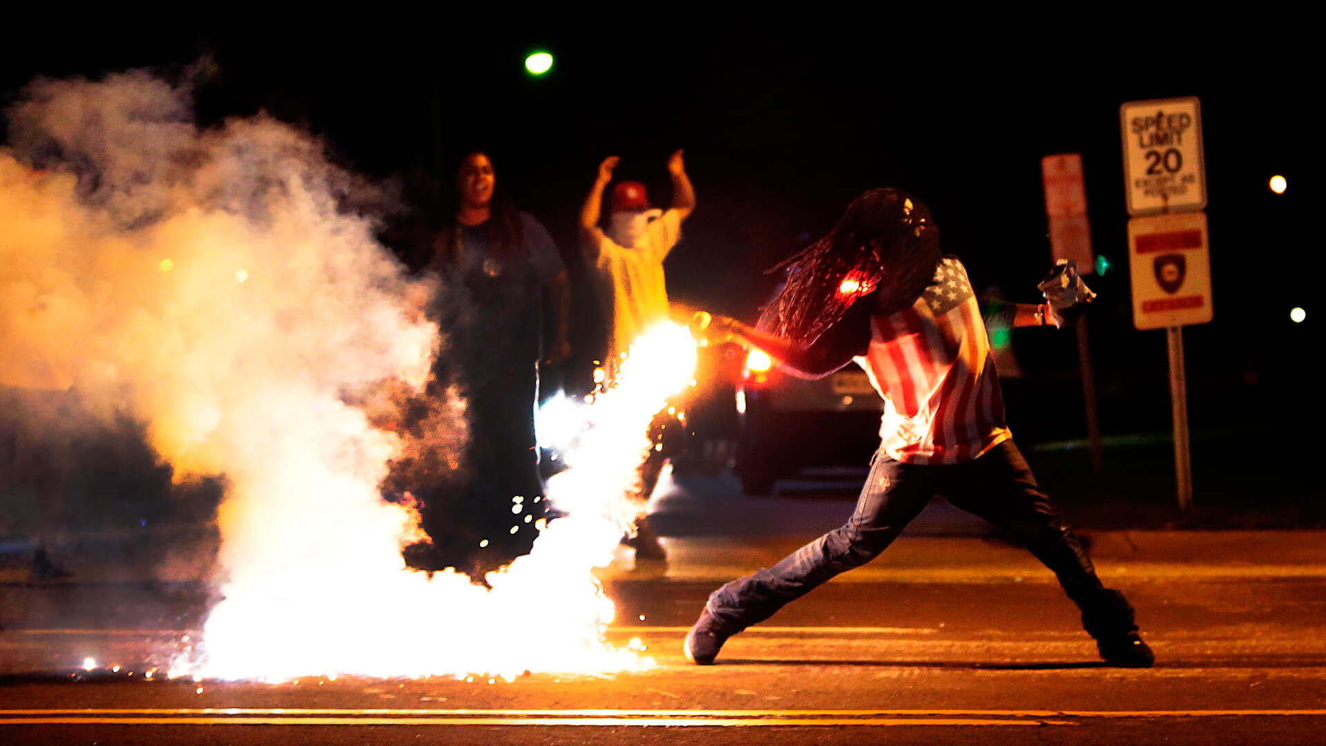 Protester Ed Crawford throws a tear gas canister away from the crowd during a protest in Ferguson in 2014.