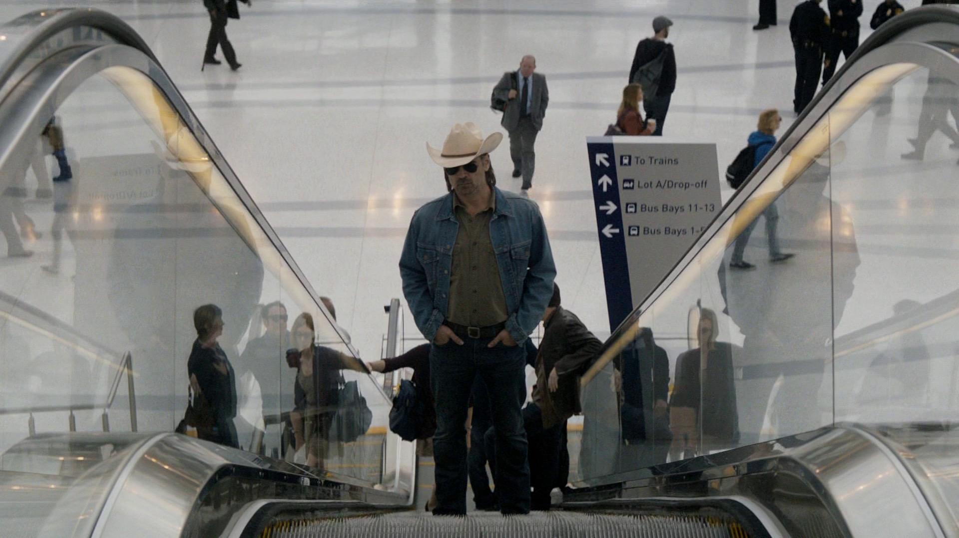 Ray ascends the escalator