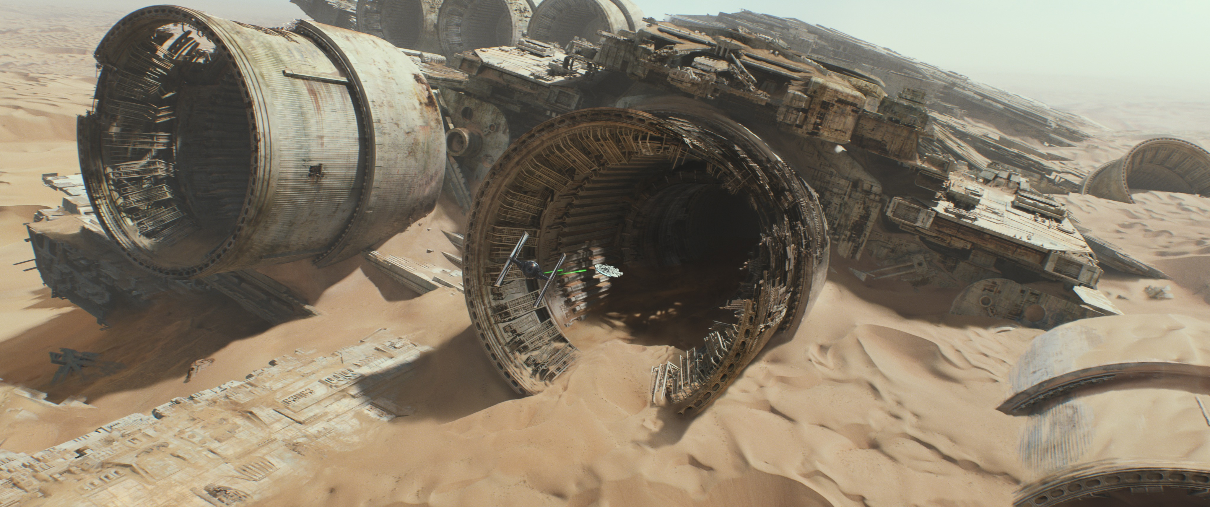 A TIE fighter and the Millennium Falcon fly toward a crashed Star Destroyer on the planet Jakku
