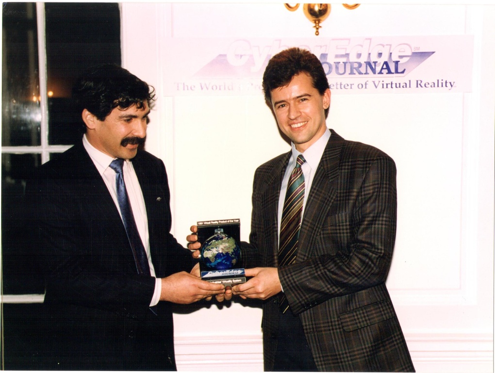 Cyberedge Journal editor Ben Delaney (left) presents an award to W Industries/Virtuality founder Jon Waldern