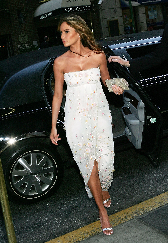 Melania Trump exiting a car in a white strapless dress.
